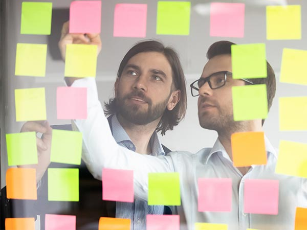 project management - two men planning a project with post-it notes